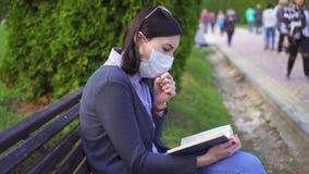 Συνεδρίαση κοριτσιών σε έναν πάγκο σε μια προστατευτική ιατρική μάσκα με ένα βιβλίο στο χέρι και τους βήχες της απόθεμα βίντεο