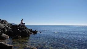 Συνεδρίαση κοριτσιών σε μια πέτρα στη θάλασσα απόθεμα βίντεο