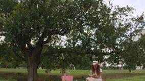 Συνεδρίαση κοριτσιών στο πάρκο που διαβάζει ένα βιβλίο κάτω από το δέντρο φιλμ μικρού μήκους