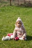 Συνεδρίαση κοριτσιών στο gardenn με το λαγουδάκι της στοκ εικόνα με δικαίωμα ελεύθερης χρήσης