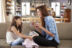 Συνεδρίαση κορών στον καναπέ που χρωματίζει στο σπίτι τα καρφιά μητέρων ` s Στοκ Εικόνες