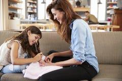 Συνεδρίαση κορών στον καναπέ που χρωματίζει στο σπίτι τα καρφιά μητέρων ` s Στοκ εικόνα με δικαίωμα ελεύθερης χρήσης