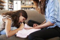 Συνεδρίαση κορών στον καναπέ που χρωματίζει στο σπίτι τα καρφιά μητέρων ` s Στοκ φωτογραφία με δικαίωμα ελεύθερης χρήσης