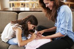 Συνεδρίαση κορών στον καναπέ που χρωματίζει στο σπίτι τα καρφιά μητέρων ` s Στοκ φωτογραφίες με δικαίωμα ελεύθερης χρήσης