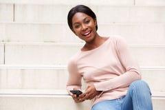 Συνεδρίαση μαύρων γυναικών χαμόγελου νέα έξω με το κινητό τηλέφωνο στοκ εικόνα