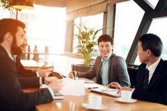 Συνεδρίαση με τους κινεζικούς επιχειρηματίες στο εστιατόριο Συζητούν το σημείο στα έγγραφα Στοκ Εικόνες