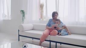 Συνεδρίαση μητέρων και γιων στον καναπέ που χρησιμοποιεί την ψηφιακή ταμπλέτα Ευτυχή mom και μικρό παιδί που χρησιμοποιούν την τα απόθεμα βίντεο