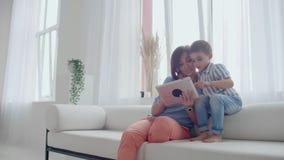 Συνεδρίαση μητέρων και γιων στον καναπέ που χρησιμοποιεί την ψηφιακή ταμπλέτα Ευτυχή mom και μικρό παιδί που χρησιμοποιούν την τα φιλμ μικρού μήκους