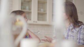 Συνεδρίαση μητέρων και κορών πορτρέτου στον πίνακα στην κουζίνα Το εύθυμα mom και το μωρό χτυπούν τα χέρια τους Σχέση απόθεμα βίντεο