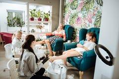 Συνεδρίαση μητέρων και κορών στις comfy πολυθρόνες που έχουν το pedicure στοκ εικόνα