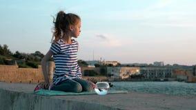 Συνεδρίαση μικρών κοριτσιών στην ακτή στρογγυλευμένο ψάρια ενυδρείο κατοικίδιων ζώων υπαίθρια το καλοκαίρι κλίμα έννοιας απόθεμα βίντεο