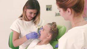 Συνεδρίαση μικρών κοριτσιών στην οδοντική καρέκλα Ο οδοντίατρος και ο βοηθός της που φαίνονται δόντια Είναι όλος μεταξύ τους χαμό απόθεμα βίντεο