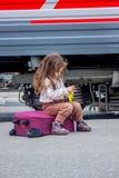Συνεδρίαση μικρών κοριτσιών στη βαλίτσα στο σιδηροδρομικό σταθμό με το τραίνο στο υπόβαθρο Στοκ Φωτογραφία