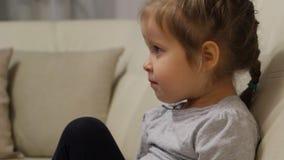 Συνεδρίαση μικρών κοριτσιών στον καναπέ και τη TV προσοχής απόθεμα βίντεο