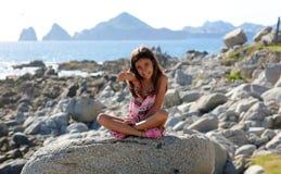 Συνεδρίαση μικρών κοριτσιών στους βράχους στο ωκεάνιο μέτωπο στη θάλασσα απότομων βράχων θερέτρου Los Cabos Μεξικό στοκ εικόνα