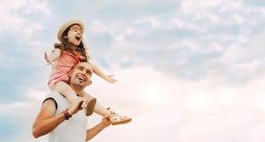 Συνεδρίαση μικρών κοριτσιών στους ώμους πατέρων ` s στοκ φωτογραφίες