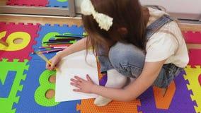 Συνεδρίαση μικρών κοριτσιών στο πάτωμα και σχέδιο απόθεμα βίντεο