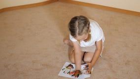 Συνεδρίαση μικρών κοριτσιών στο πάτωμα με τα έγγραφα και το σχέδιο με τα watercolors στο σπίτι απόθεμα βίντεο