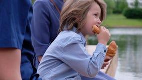 Συνεδρίαση μικρών παιδιών από τον ποταμό με τους γονείς και την κατανάλωσή του croissant απόθεμα βίντεο