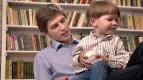 Συνεδρίαση μικρών παιδιών με τη νέα σφαίρα του πατέρων και εκμετάλλευσης, ράφια με το υπόβαθρο βιβλίων απόθεμα βίντεο