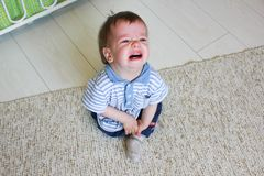 Συνεδρίαση μικρών παιδιών στο πάτωμα, αυτός ` s που ανατρέπεται και που φωνάζει Το chil Στοκ Εικόνα