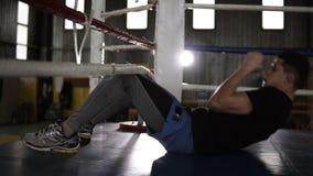 Συνεδρίαση μπόξερ στο πάτωμα στο εγκιβωτίζοντας δαχτυλίδι που εκπαιδεύει τους κοιλιακούς μυς Ανυψωτικός κορμός μέχρι τα εγκιβωτίζ φιλμ μικρού μήκους