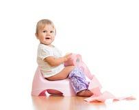 Συνεδρίαση μωρών στο δοχείο αιθουσών με το χαρτί τουαλέτας στοκ φωτογραφία