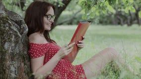 Συνεδρίαση νέων κοριτσιών στη χλόη στο πλαίσιο των σημειώσεων δέντρων και γραψίματος απόθεμα βίντεο