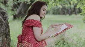 Συνεδρίαση νέων κοριτσιών στη χλόη στο πλαίσιο των σημειώσεων δέντρων και γραψίματος φιλμ μικρού μήκους