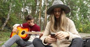 Συνεδρίαση νεαρών άνδρων και γυναικών στο δάσος με την κιθάρα απόθεμα βίντεο