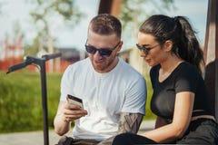 Συνεδρίαση νεαρών άνδρων και γυναικών στο πάρκο και εξέταση την κινητή τηλεφωνική οθόνη στοκ φωτογραφίες