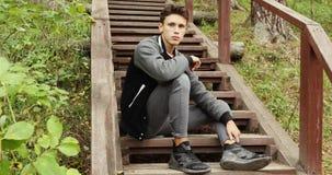 Συνεδρίαση νεαρών άνδρων στα σκαλοπάτια στο δάσος απόθεμα βίντεο