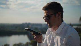 Συνεδρίαση νεαρών άνδρων στην ακτή που έχει τη συνομιλία με το όργανο καταγραφής μηνυμάτων φωνής στο smartphone έξω στο ηλιοβασίλ απόθεμα βίντεο
