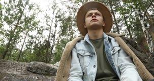 Συνεδρίαση νεαρών άνδρων στον απότομο βράχο στο δάσος απόθεμα βίντεο