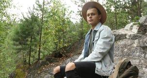 Συνεδρίαση νεαρών άνδρων στον απότομο βράχο στο δάσος φιλμ μικρού μήκους