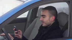 Συνεδρίαση νεαρών άνδρων στο αυτοκίνητο, που χρησιμοποιεί το smartphone του απόθεμα βίντεο
