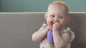 Συνεδρίαση νηπίων στον καναπέ, λαστιχένιο παιχνίδι εκμετάλλευσης στο στόμα, πρώτα δόντια μωρών, υγεία απόθεμα βίντεο
