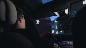 Συνεδρίαση οδηγών στο αυτοκίνητο πολυτέλειας στο βροχερό καιρό, νυχτερινή κίνηση, κίνδυνος ατυχήματος απόθεμα βίντεο