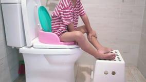 Συνεδρίαση παιδιών στο κύπελλο τουαλετών απόθεμα βίντεο