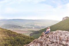 Συνεδρίαση πατέρων και κορών στο βράχο βουνών στοκ φωτογραφία