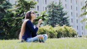 Συνεδρίαση πικραλίδων φυσήγματος κοριτσιών σε ένα πάρκο πόλεων στη χλόη, υπόλοιπο στην πόλη απόθεμα βίντεο
