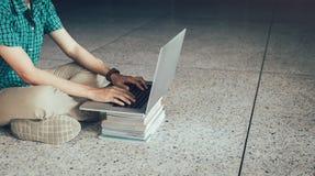 Συνεδρίαση σπουδαστών εφήβων στο πάτωμα που χρησιμοποιεί το φορητό προσωπικό υπολογιστή στο libra στοκ εικόνα