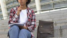 Συνεδρίαση σπουδαστών στα σκαλοπάτια και γράψιμο των στόχων της στα σημειωματάρια, σύγχρονη εκπαίδευση απόθεμα βίντεο