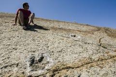 Συνεδρίαση τουριστών κοντά σε διάφορο απολίθωμα δεινοσαύρων trackways, Sesi Στοκ εικόνα με δικαίωμα ελεύθερης χρήσης