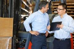 Συνεδρίαση των επιχειρηματιών από forklift το truck στην αποθήκη εμπορευμάτων Στοκ Εικόνα