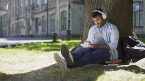 Συνεδρίαση τύπων αναμιγνύω-φυλών κάτω από το δέντρο στα ακουστικά που γράφουν στο σημειωματάριο, συγγραφέας τραγουδιού απόθεμα βίντεο