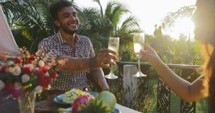 Συνεδρίαση CHAMPAGNE ποτών ευθυμιών ζεύγους στον πίνακα που έχει το γεύμα στο πεζούλι, τον ελκυστικούς άνδρα και τη γυναίκα που μ φιλμ μικρού μήκους
