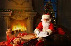 Συνεδρίαση Santa στο χριστουγεννιάτικο δέντρο, τις επιστολές Χριστουγέννων εκμετάλλευσης και την κατοχή ενός υπολοίπου από την εσ Στοκ φωτογραφίες με δικαίωμα ελεύθερης χρήσης