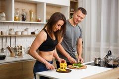 Συνειδητό ζεύγος υγείας που μαγειρεύει το λίγων θερμίδων γεύμα στοκ φωτογραφίες