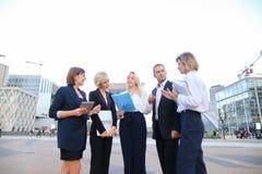 Συνεργάτες επιχειρήσεων που συμβουλεύουν και που καλούν από το smartphone έξω στοκ εικόνα με δικαίωμα ελεύθερης χρήσης